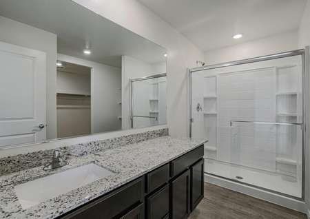 Incredible master bathroom with granite countertops and a walk-in shower.