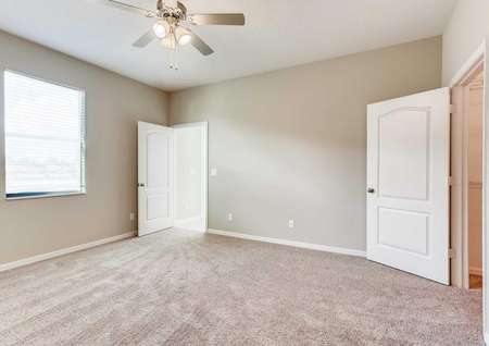 The Santa Maria model home's master bedroom. Spacious room with carpet, white baseboards and tan walls