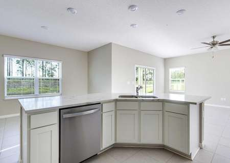 The kitchen island in the Mykkafloor plan with a quartz countertops, white cabinets and a stainless steel dishwasher.