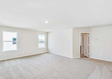 Carpeted master bedroom with two windows and its own full bathroom.