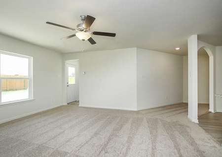 Trinity great room with carpeted floors, access to the dining room, and overhead brown ceiling fan