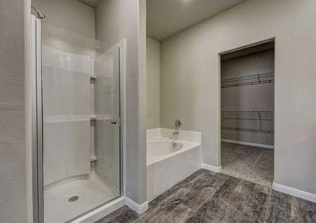 Cypress master bath with walk-in shower, white bathtub, and brown floors