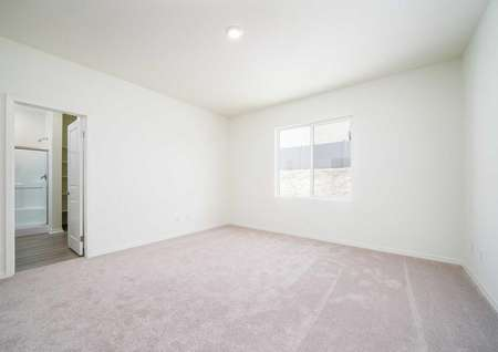 Laguna master bedroom with carpeted floors, recessed light, and access to private bathroom