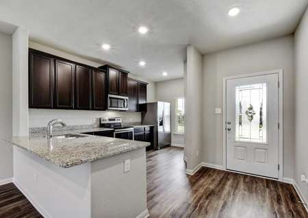 Victoria single family house kitchen with dark wood cabinets, can lights, and gray colored granite counter with undermount sink