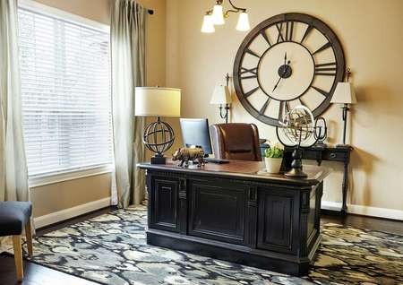 Kingston model home with office furniture, throw rug, and large clock mounted to the wall
