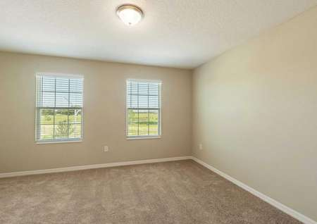 A spare bedroom in the Tuscany floor plan with light brown carpet, white baseboards, tan walls and two windows.