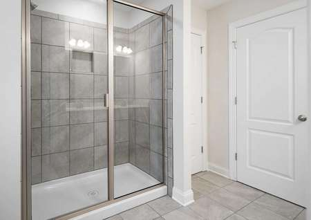 Fripp master bathroom with custom tile shower, tiled floors, and white doors and trims