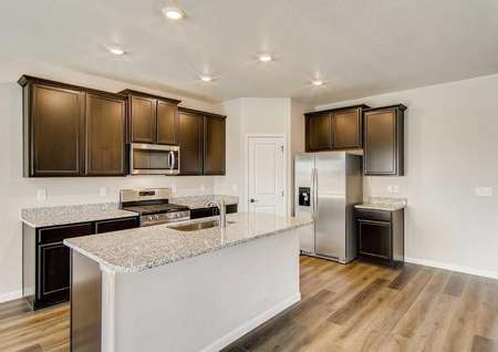 Pike plan's kitchen with granite countertops & anisland that has a sink.
