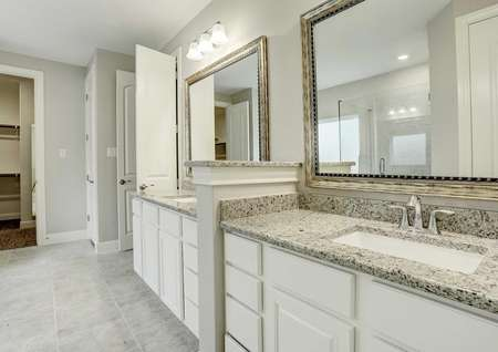 Bradley master bath with white ceramic flooring, dual vanities with granite tops, and framed wall mirrors