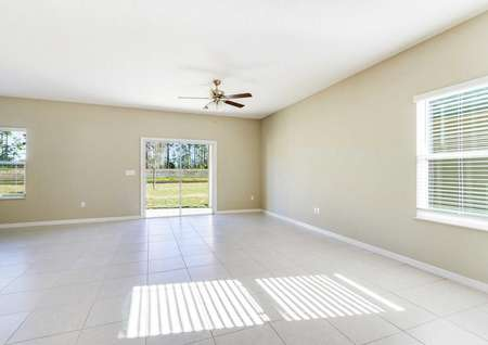 Spacious living room with tile flooring, white baseboards, tan walls and a ceiling fan in the Tomoka floor plan.