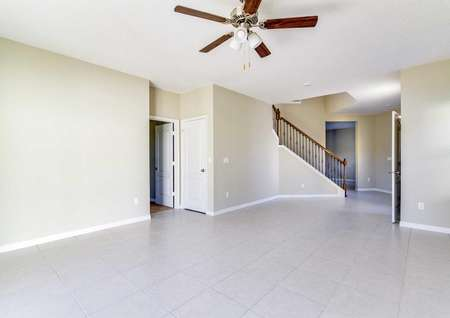 Tile flooring in the Wekiva floor plan's living room with a ceiling fan and a view of the stairs that lead upstairs.