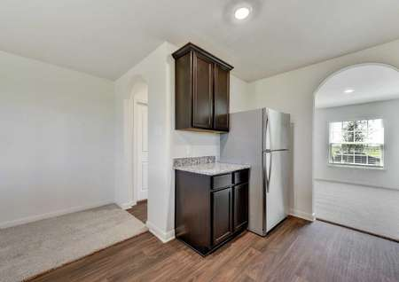 Frio kitchen counter with stainless steel refrigerator and archway entry to dining room
