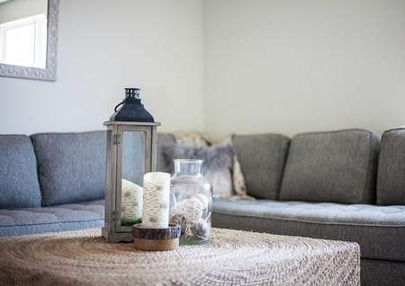 Staged living room with grey couch and white colored coffee table with vase and candle sitting on it.