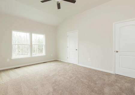 The Mid Atlantic Newport master bedroom shown with carpet and ceiling fan.
