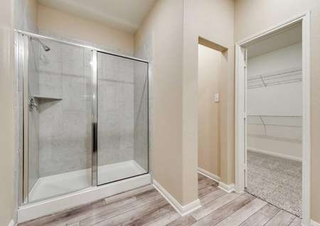 Erie master bath with tile shower, walk-in closet, and tiled floors