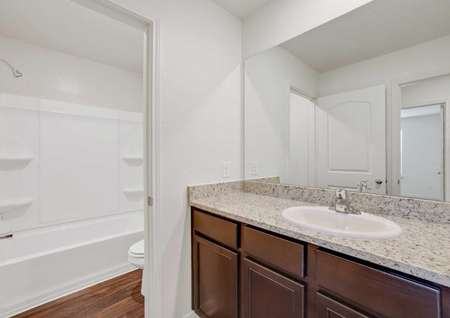 The Rio model home's second bathroom with granite countertops, dark brown cabinetry and shower and tub combo