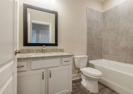 Full bathroom with a granite countertop sink and modern hardware.