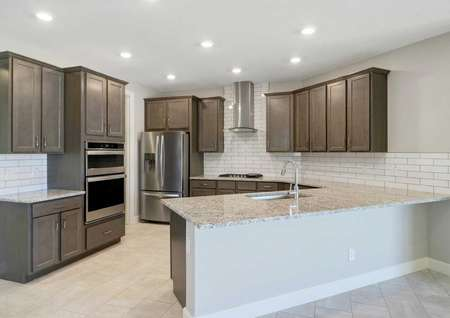 Powell kitchen with recessed ceiling lights, granite countertops, and brown cabinetry