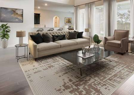 Staged living room with a fireplace, tan couch and soaring ceilings.
