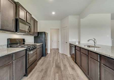 Cypress finished kitchen with black appliances, undermounted sink, and light color granite counters