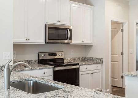 Alamance kitchen with light color granite counters, white cabinets, and undermounted sink