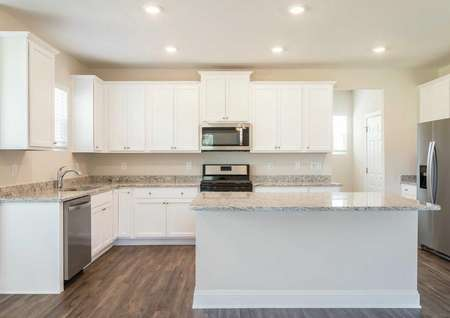 Craven finished kitchen with stainless steel appliances, granite counters, and white cabinetry