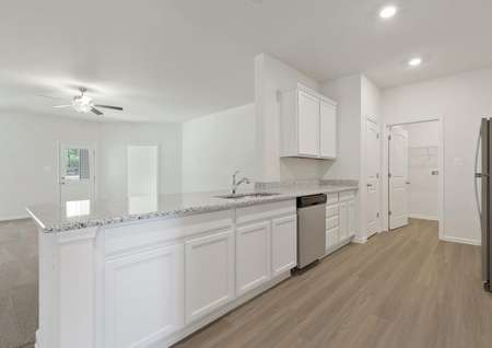 Spacious kitchen with sprawling granite breakfast bar overlooking family room with ceiling fan and door to backyard patio, white cabinets, plank flooring, recessed lighting, stainless dishwasher, pantry and laundry room.