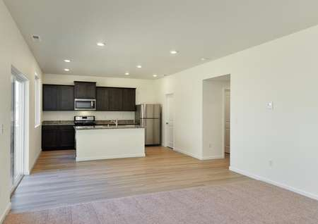 Open concept living, dining, kitchen with carpet and plank flooring, dark cabinetry in kitchen.