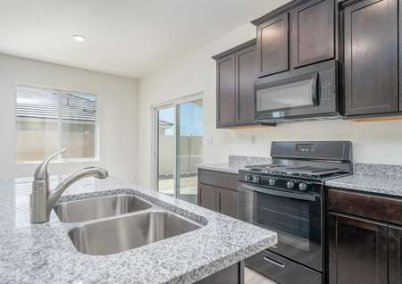 Balboa kitchen with undermount sink, granite counters, and brown cabinets
