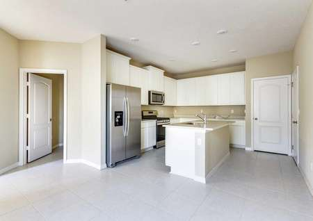 The Wekiva floor plans kitchen that has an island with a sink, quartz countertops and stainless steel appliances.