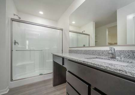 Venice bathroom with walk-in shower, gray granite counters, and brown cabinetry