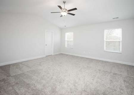 Fripp bedroom with two windows with blinds, overhead ceiling fan, and soft brown carpets