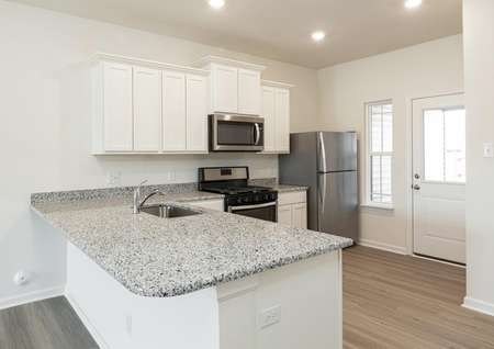 Kitchen with gray granite counters, white cabinets with molding, recessed lights, plank flooring, window to back yard.