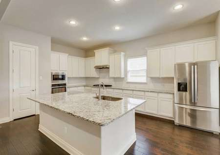 Fairview house kitchen finished with stainless steel refrigerator, white cabinets, and light fixtures in the ceiling