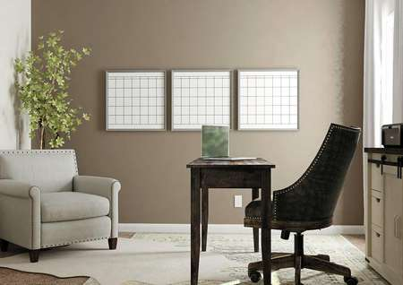 Rendering of a secondary bedroom with   window and brown accent wall decorated as an office with desk, file cabinet   and gray armchair.