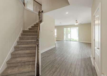 Entrance of two-story Verona floor plan with a beautiful staircase, luxury vinyl plank flooring and plenty of natural light entering the home.