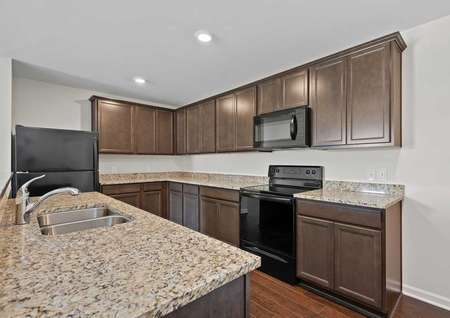 A view of the Clairborne model kitchen with granite countertops, a stainless steel sink, black appliances, light brown cabinets with crown molding, and brought together withvinyl flooring