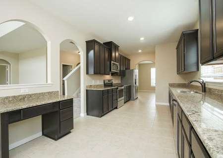 Kitchen with tech station, tile flooring, granite counters, stainless appliances, and dark cabinets in the Redwood model