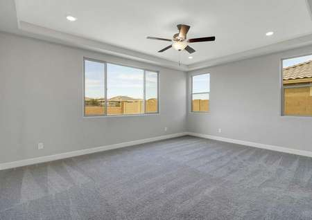 Hawley bedroom design with grey carpet, three windows, and tall ceilings with fan