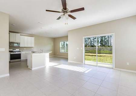 Spacious living room with a ceiling fan and asliding glass door that goes to the backyard in the Mykka floor plan.