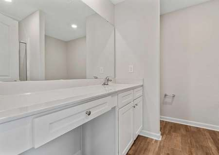 Allatoona bathroom with extended make-up vanity, wood-like tile flooring, and white fixtures