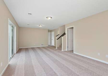 Spacious, carpeted game room on lower level of home with sliding glass door.