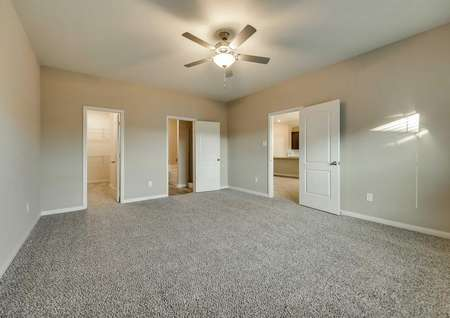 Master bedroom with tan walls, white trim and brown carpet.