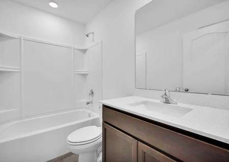 Sunnyside bathroom with white counter, shower and bathtub unit, and brown vanity