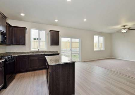Cypress kitchen with granite counters, wood cabinets, and recessed lights overlooking living room