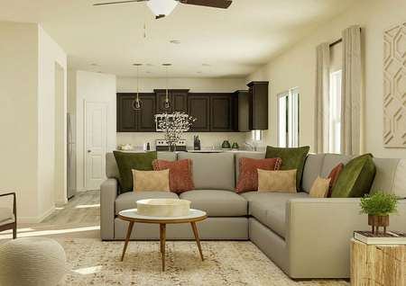 Rendering of the   living room with ceiling fan and tan walls decorated with a gray sectional   couch, round coffee table and two armchairs. The brown cabinets of the   kitchen are visible in the background.