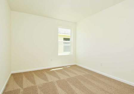 Secondary carpeted bedroom of the Juniper floor plan with white walls and a single hung window covered byblinds.