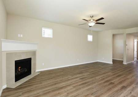 Larch great room with overhead light and fan, white trimmed walls, and wood looking floors