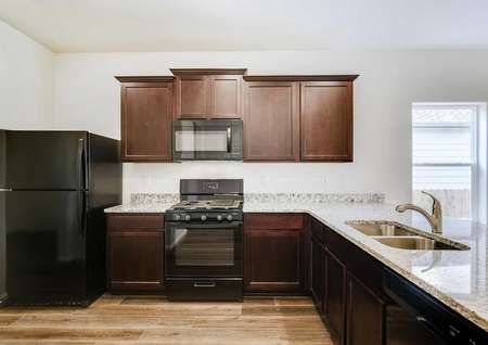Arapaho kitchen with dark wooden cabinets, black appliances, and granite counters