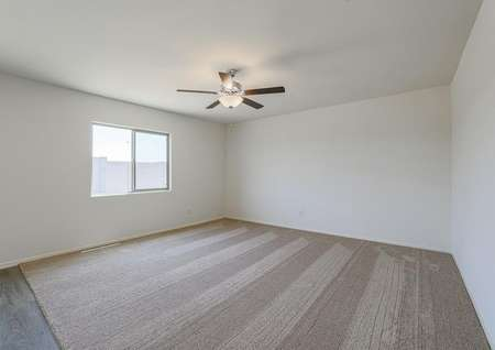 Spacious family room with tan carpet, ceiling fan and windows.